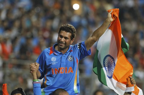 India's Tendulkar waves national flag as he is carried by his teammates after they beat Sri Lanka in the ICC Cricket World Cup final match in Mumbai